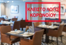 Defocused view of interior of an upmarket restaurant empty and closed with Greek notice saying Closed due to Coronavirus