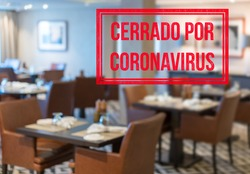 Defocused view of interior of an upmarket restaurant empty and closed with spanish notice saying Closed due to Coronavirus