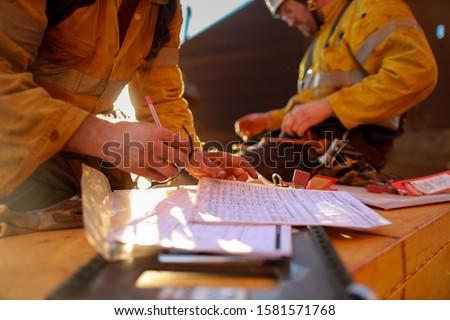 Defocused worker hand checking on JHA Job Hazard Analysis before signing hot work permit to work on isolation safety control lock box prior to work defocused senior supervisor seating background Zdjęcia stock ©