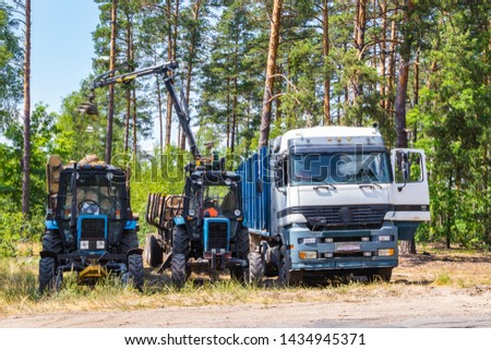 Deforestation and automatic loading on a truck, the concept of the forest industry and the constant earnings of forest workers, pine forest is exported for further processing and delivery of material  #1434945371