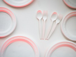 degradable plastic forks and spoons and disks arranged on white background, to protect environment by using biodegradable plastic material is one of better ways.