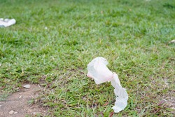 Degraded plastic littering on the field grass