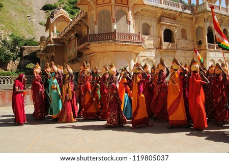 DEHLI, INDIA - SEPT 24 2012:  Colorful indian women wearing saris and carrying jars on their head to celebrate the return of the pilgrims on sept 24, 2012 in Delhi, India