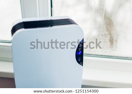 Dehumidifier with touch panel, humidity indicator, uv lamp, air ionizer, water container works by wet window in flat.