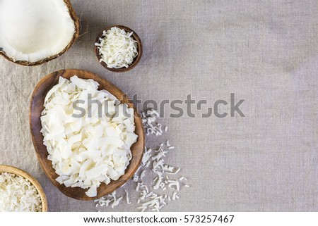 Dehydrated coconut flakes in wooden bowl. #573257467