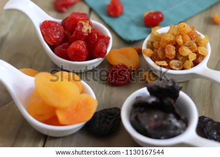 Dehydrated fruits like strawberries, apricots, plums and raisins on a wooden background and fabric. #1130167544