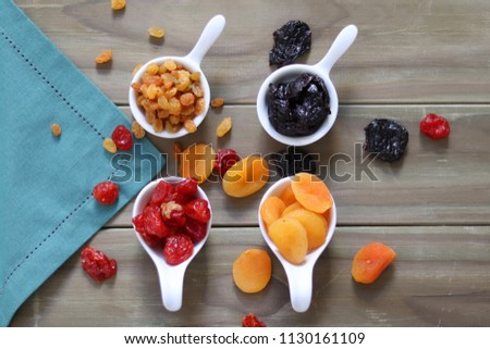 Dehydrated fruits like strawberries, apricots, plums and raisins on a wooden bottom and fabric with top view. #1130161109