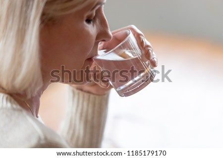 Dehydrated healthy thirsty senior old woman drinking filtered pure water, middle aged mature lady holding glass quenching thirst for body refreshment, energy recovery, rejuvenation, hydration concept