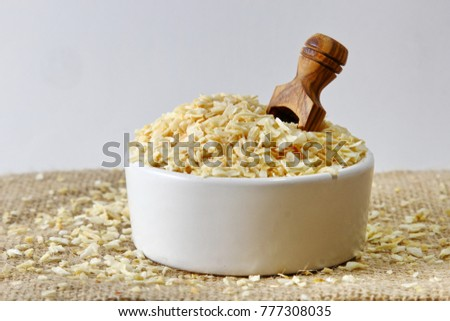 Dehydrated Onion flakes in a ceramic bowl #777308035