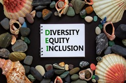 DEI, diversity, equity, inclusion symbol. Words DEI, diversity, equity, inclusion on a beautiful white note, black background. Sea stones and seashells. DEI, diversity, equity, inclusion concept.