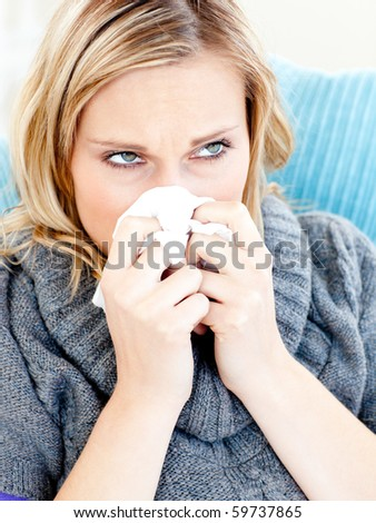 Dejected woman lying on a sofa with tissues and blowing against a white background