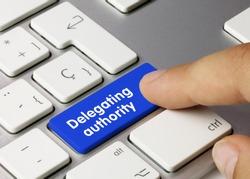 Delegating authority Written on Blue Key of Metallic Keyboard. Finger pressing key.