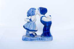 Delft Blue Figurine of kissing Dutch couple. Souvenir from Holland/Netherlands. Isolated on white background.