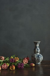 Delft blue vase with pink, yellow, red and purple tulips on wooden table.