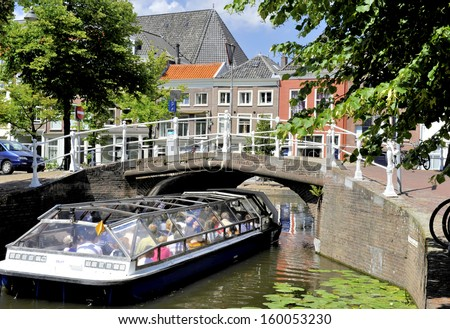 DELFT,HOLLAND-JULY 18,2010;Tourist sight seeing boat nearing a bridge over a canal. July,18,2010 Delft,Holland