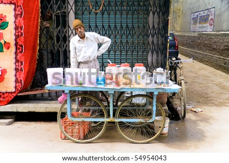 DELHI - DECEMBER 2: Mobile tea stall merchant selling sweets, biscuits and drinks on December 2, 2007 in Delhi, India. It is local tradition to drink tea from the street. - stock photo