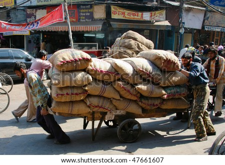 DELHI - FEBRUARY 12: Hard working indians pushing heavy load through streets on February 12, 2008 in Dehli, India. Human labour is still cheaper than motorised vehicles.