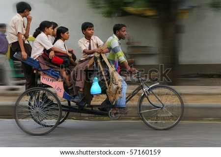 DELHI, INDIA - JULY 31: Big Indian family riding a cycle rickshaw in the streets of Delhi July 31, 2008 in Delhi, India