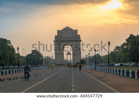 DELHI, INDIA, MARCH 10, 2017: View of Rajpath road New Delhi near India Gate at sunrise with morning walkers enjoying the fresh air. The India Gate, is a war memorial and a notable city landmark. #604547729