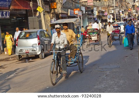 DELHI, INDIA - NOV 8: Rickshaw rider transports passenger early morning on November 08,2011 in Delhi, India. Cycle rickshaws were introduced in Delhi in the 1940's and have a fixed quota of licenses.