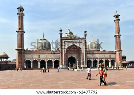 DELHI, INDIA - OCTOBER 24:  A group of worshipers walk on courtyard of Jama Masjid Mosque in Delhi on October 24, 2009. Jama Masjid is the principal mosque of Old Delhi in India. - stock photo