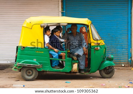 Delhi, India - October 27, 2009: Young children crammed into a private auto rickshaw waiting patiently to be transported to school while driver talks on mobile phone without any care in the world