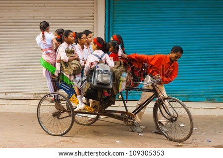 Delhi, India - October 27, 2009: Young girls crammed into an overloaded private cycle rickshaw riding uncomfortably to school in the morning