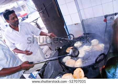 DELHI - OCTOBER 28: Two men preparing Puri in small roadside restaurant on October 28, 2007 in Delhi, India. Chapatis are the staple diet of all Indians.
