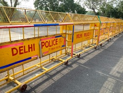 Delhi Police barricades stand on the Road.