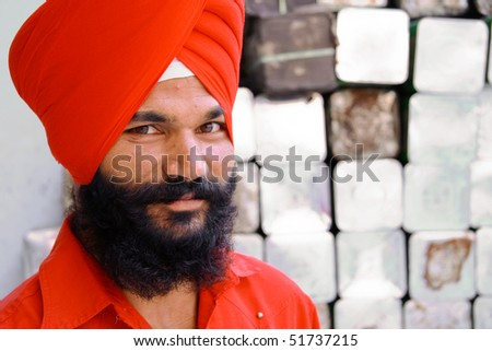 DELHI - SEPTEMBER 22:  Young fashionable Sikh with red turban at Sis Ganj Gurdwara on September 22, 2007 in Delhi, India. Worldwide there are about 25 million Sikhs.