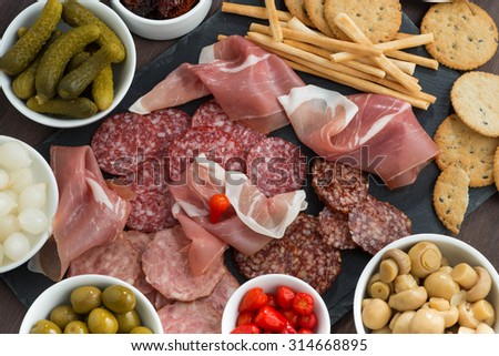 deli meat snacks, sausages and pickles on a blackboard, top view, horizontal