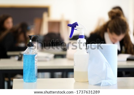 Deliberately blurred students in the background working on classwork. Hand sanitizer sanitiser pump with disinfectant spray bottle in the foreground. Corona virus Covid 19 education school theme.