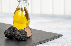 Delicacy mushroom black truffle with olive oil bottle on a light background .