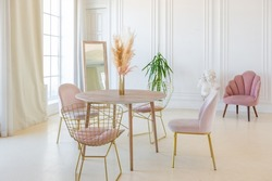 delicate and cozy light interior of the living room with modern stylish furniture of pastel pink color and white walls with stucco moldings in daylight
