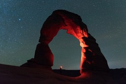Delicate Arch in Arches National Park is illuminated by a hiker with a red light headlamp.