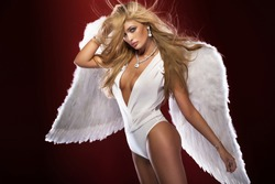 Delicate beautiful blonde woman posing with angel wings. Studio shot.