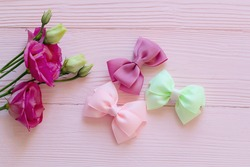 delicate children's hair bands and barrettes on a pink wooden background, Bright children's hair accessories on a pink wooden background, Children's hair bands in the form of bows
