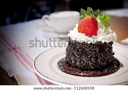 Delicate chocolate cake with whipped cream and strawberry.