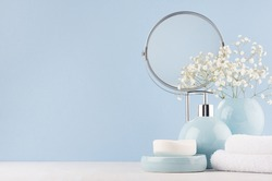 Delicate elegant ceramic decorations for bathroom - soft blue bowls, vase, white flowers, towel and soap on white wood table. Modern bath interior.