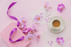 Delicate flatlay composition with morning cup of coffee with milk or cappuccino, letters, pink gift bag and orchid flowers on light pink background. Beautiful breakfast concept