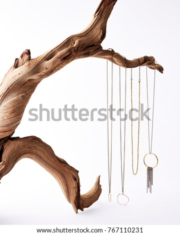 Delicate hand crafted gold and silver necklaces hanging from a twisted driftwood branch on a white background #767110231