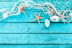 Delicate nautical border with fishing net, sea shells and starfish on a background of colourful turquoise blue painted wooden boards with copyspace for your text