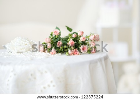 Delicate pink roses and pearl beads on the table