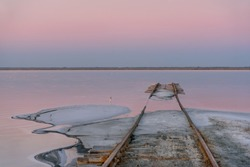 Delicate pink sunrise over a salt lake, rails going into the water and salt on the shore in the foreground. Lake Bursol, Altai, Russia.