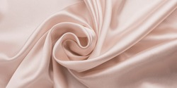 Delicate smooth soft pink silk bedsheet, abstract fabric background with waves. Beige shiny textile texture. Satin folds, luxury fashion. Glossy clothes.