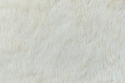 delicate soft background of plush fabric folds on white background. Copy space. Flat lay. loose folds on the fabric of faux fur of lilac color. Details of warm winter clothes