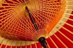 delicate structure of a vivid vermilion Japanese umbrella
