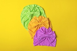 Delicate turbans for women, girls or baby. Turban fashion or bandana hair accessories for the beach and travel on yellow background.