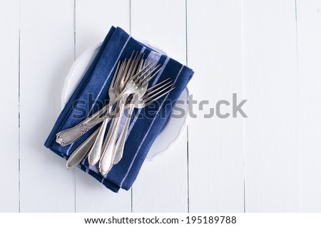 Delicate vintage silverware on blue linen napkin in a plate, antique cutlery om white wooden board, country kitchen background