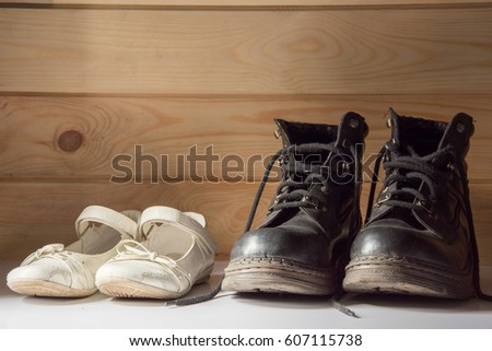 Delicate, white girl shoes and heavy, strong, black army boots standing in front of a wooden wall #607115738
